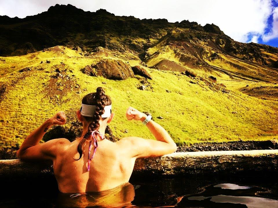 An adventure traveler flexing back muscles in a hot spring in Iceland.
