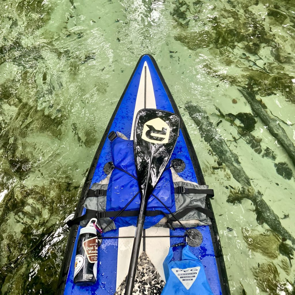 A view of a paddle board from above showing just how clear the water of Rock Springs Run is.