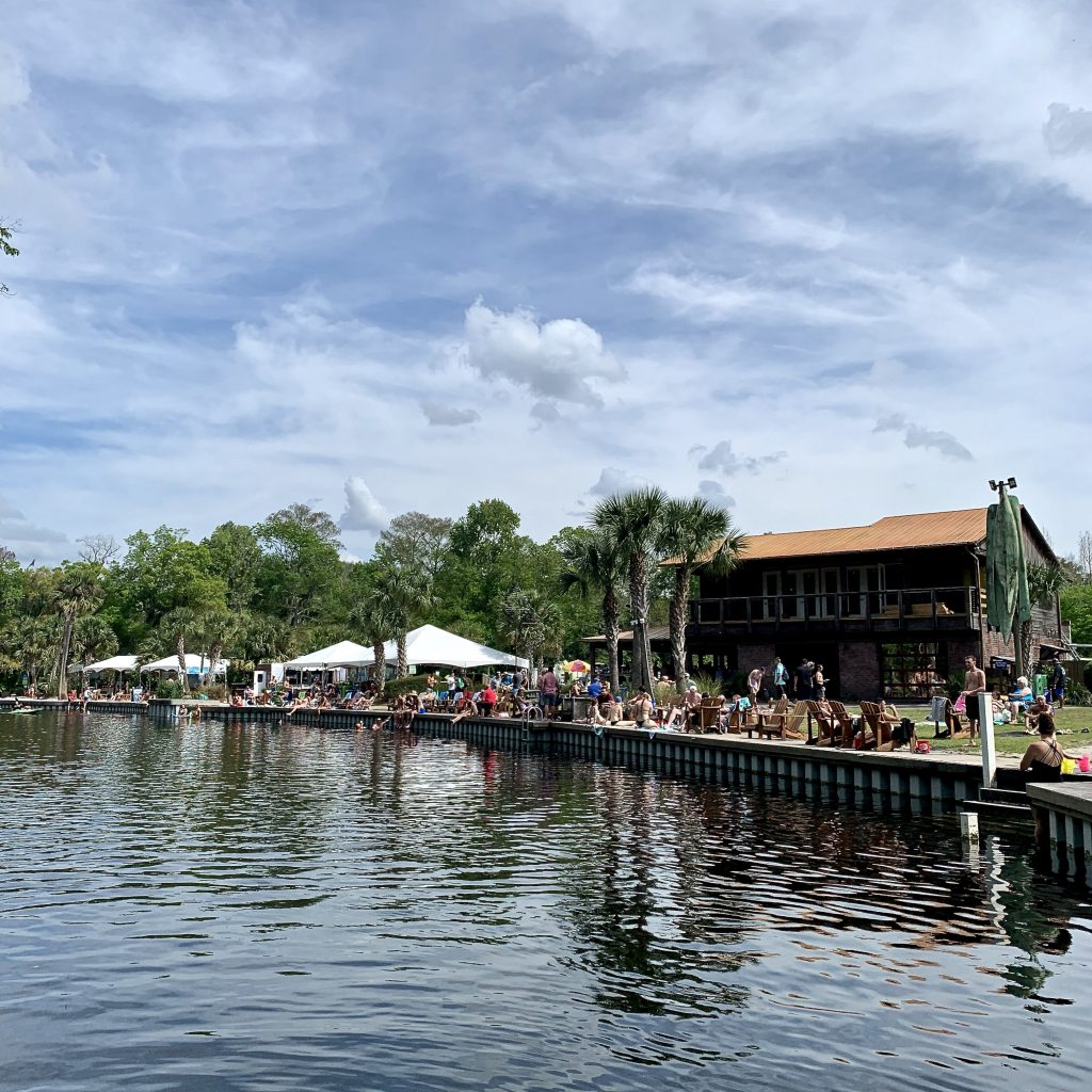 People line the banks of Wekiva Island while they enjoy drinks and food.