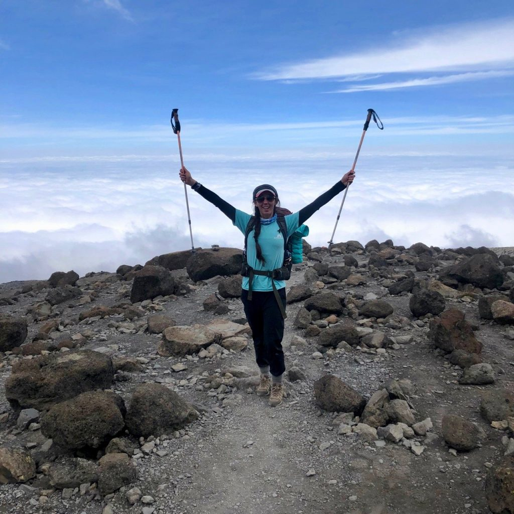A hiker poses with trekking poles lifted towards the sky.