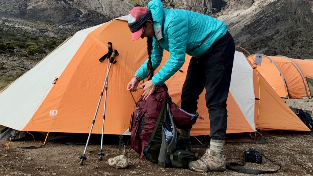 Hiker sorts through backpack and other gear while climbing Kilimanjaro.