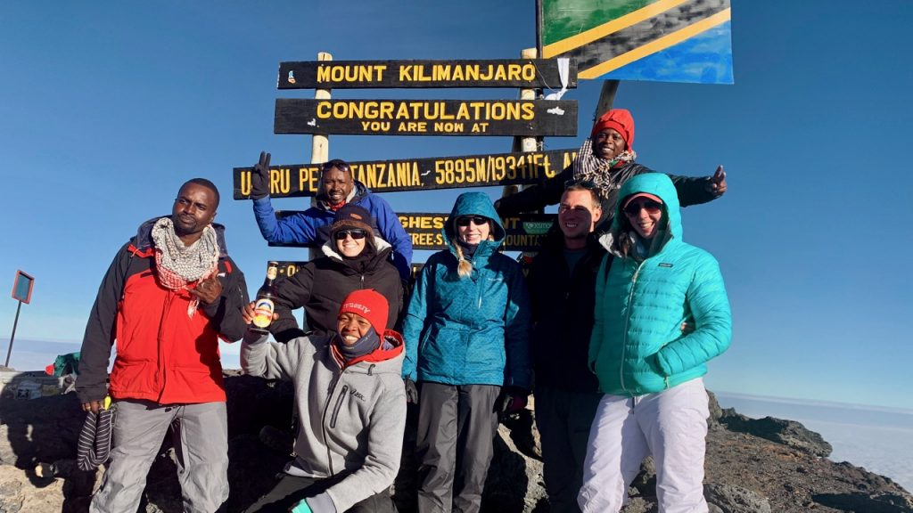 Hikers stand with their guides for a photo in front of the sign at the peak of Kilimanjaro.