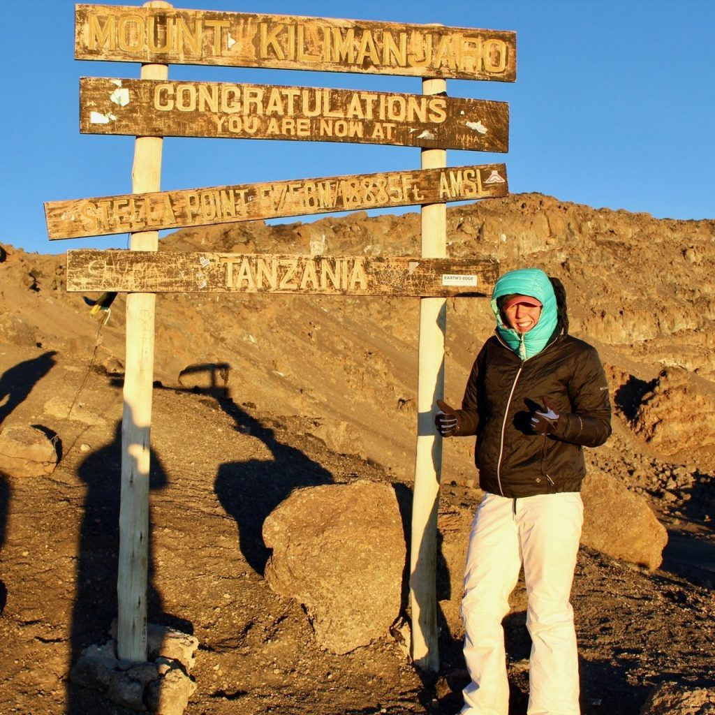 Hiker poses with thumbs up at Stella Point on summit day on Kilimanjaro.