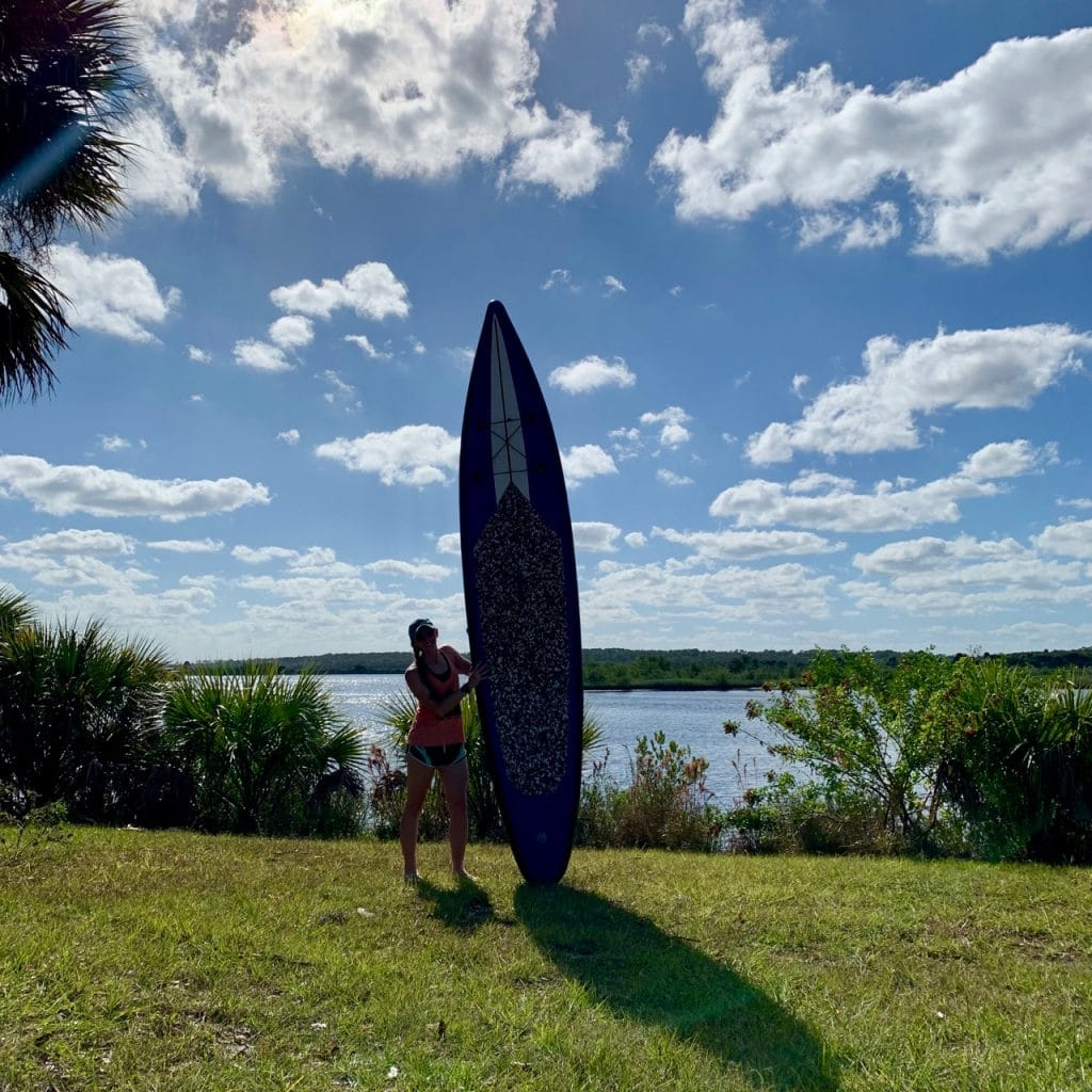 A stand up paddle boarder poses with her board in front of the Tomoka River at the Tomoka State Park.