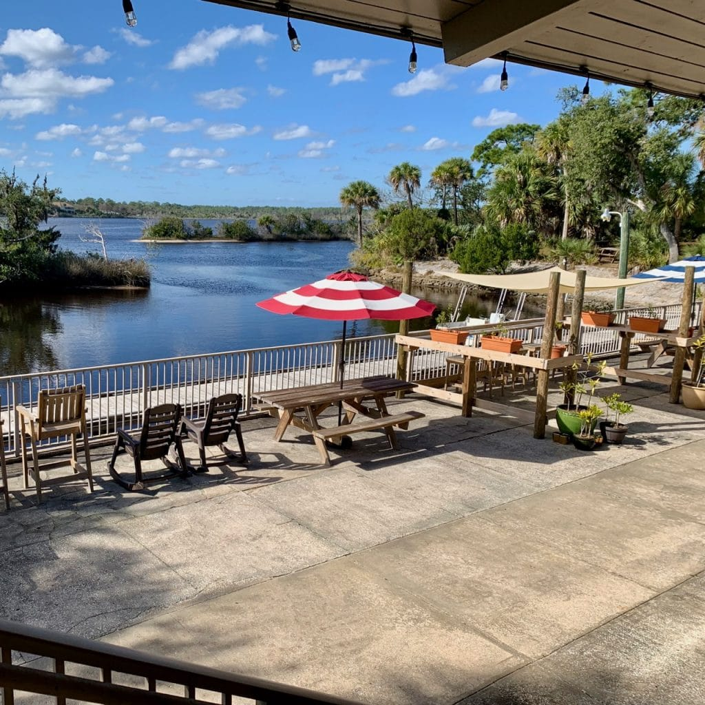 A large patio sits along the water along the Tomoka River.