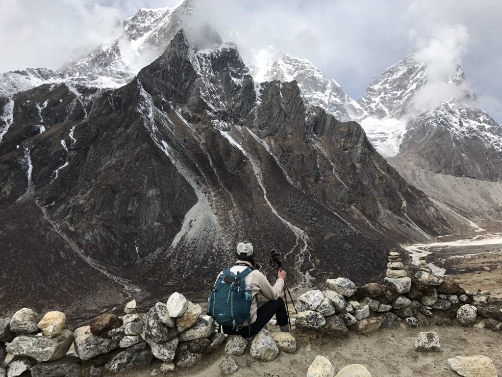 Trekker overlooking the Himalayas when trekking from Dingboche to Lobuche.