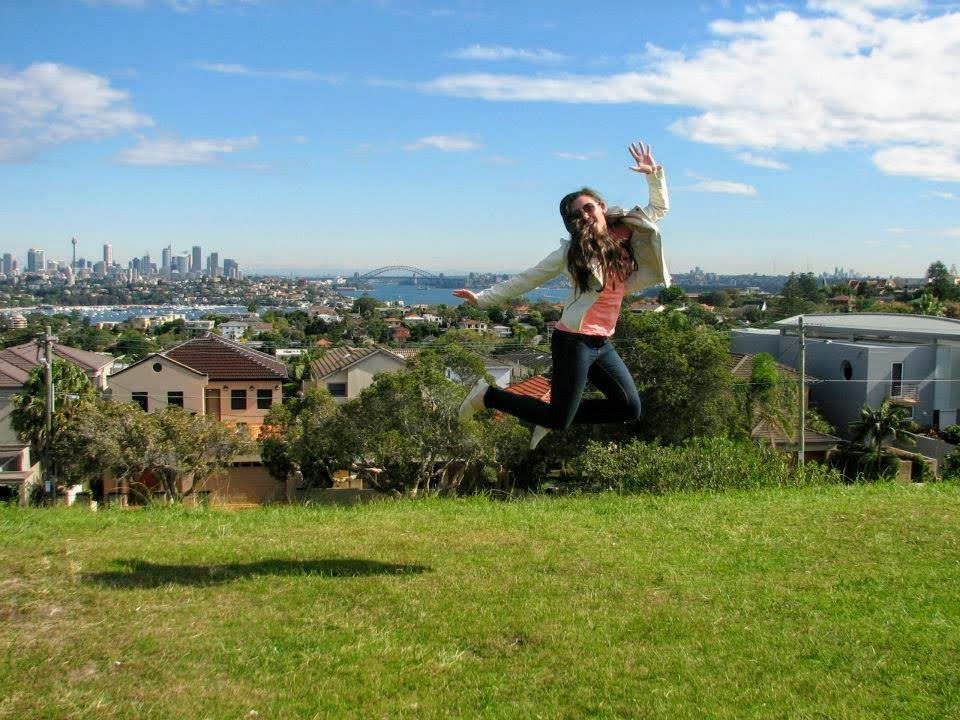 An adventure traveler jumping in front of Sydney Harbor.