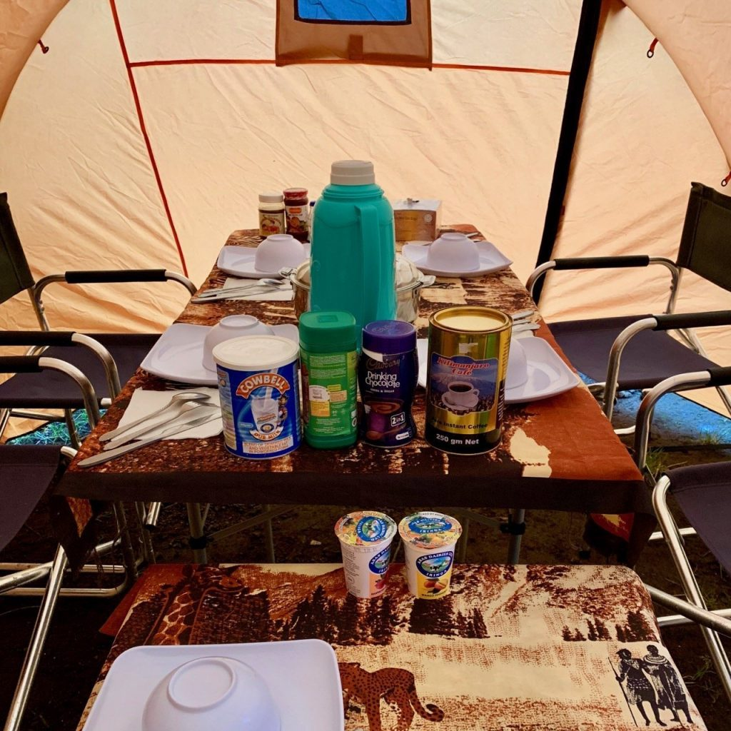 The mess tent set up by Kilimanjaro Backcountry Adventures has various drinks and food set for a meal on Kilimanjaro.