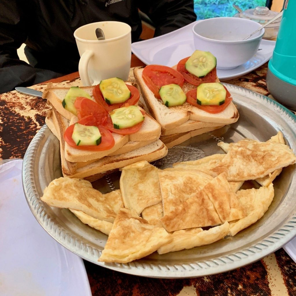 A plate of food consisting of eggs, bread and vegetables provided by Kilimanjaro Backcountry Adventures.