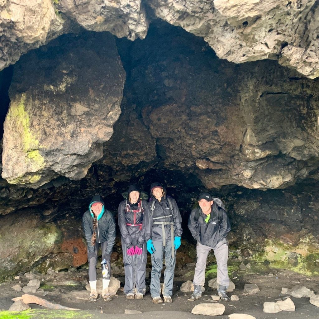 Four hikers in a cave along the Machame route to summit Kilimanjaro.