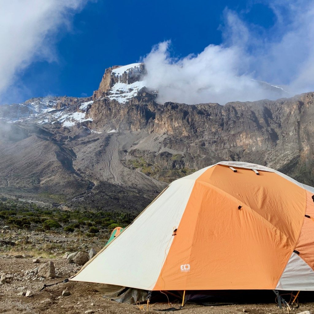 A tent set up in front of Kilimanjaro with a few clouds covering the peak.