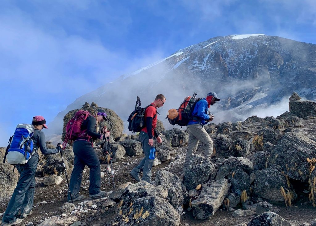 Hikers along the Machame Route with the peak of Kilimanjaro in the background.
