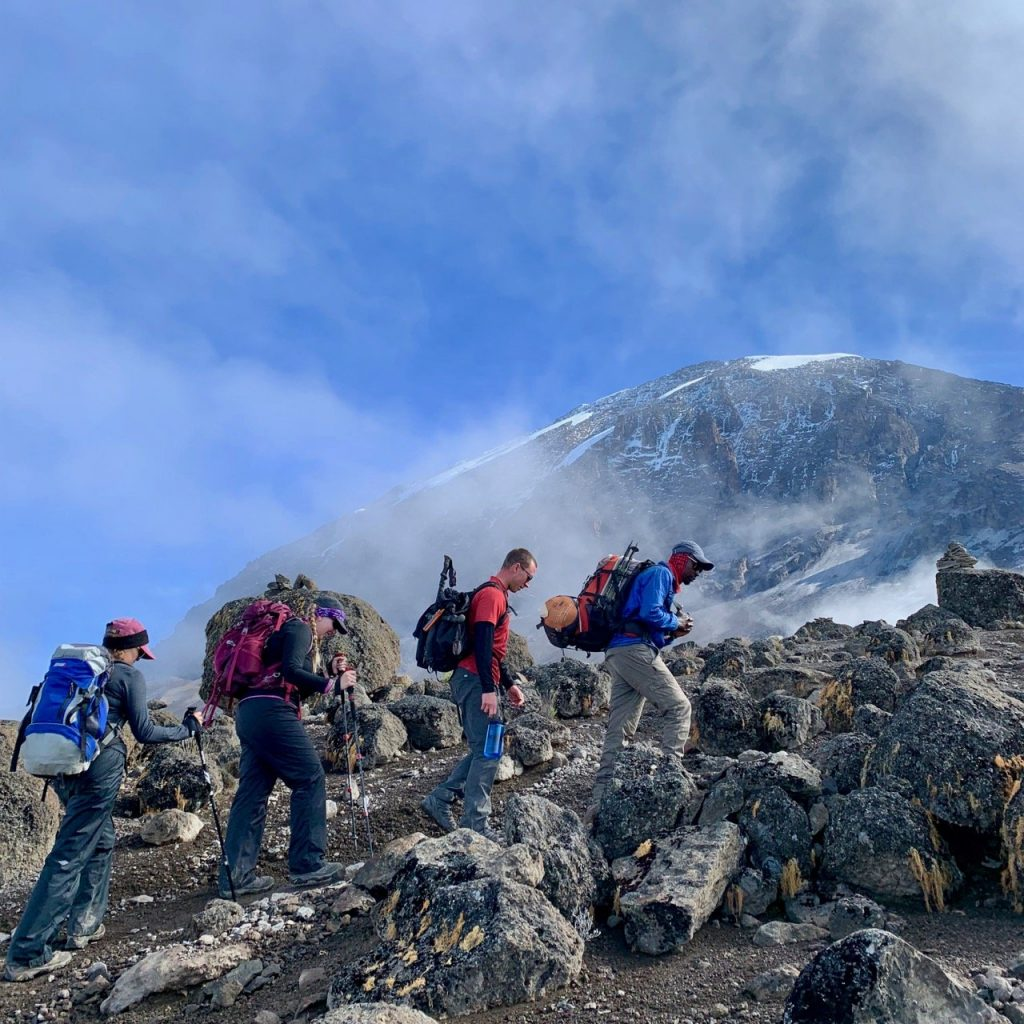 Hikers climb a steep ascent with Kilimanjaro in the background.