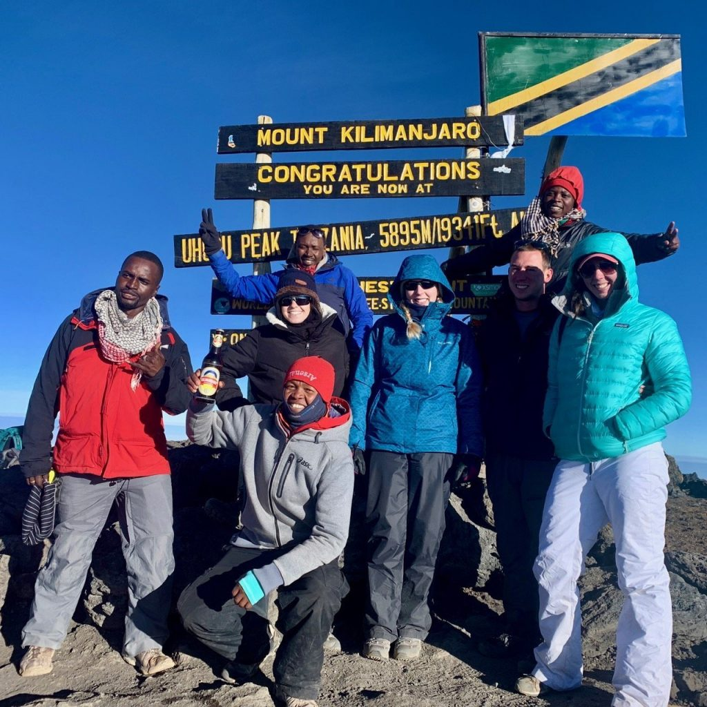 The team celebrating a successful climb to the summit of Kilimanjaro in front of the Congratulations sign at Uhuru Peak.