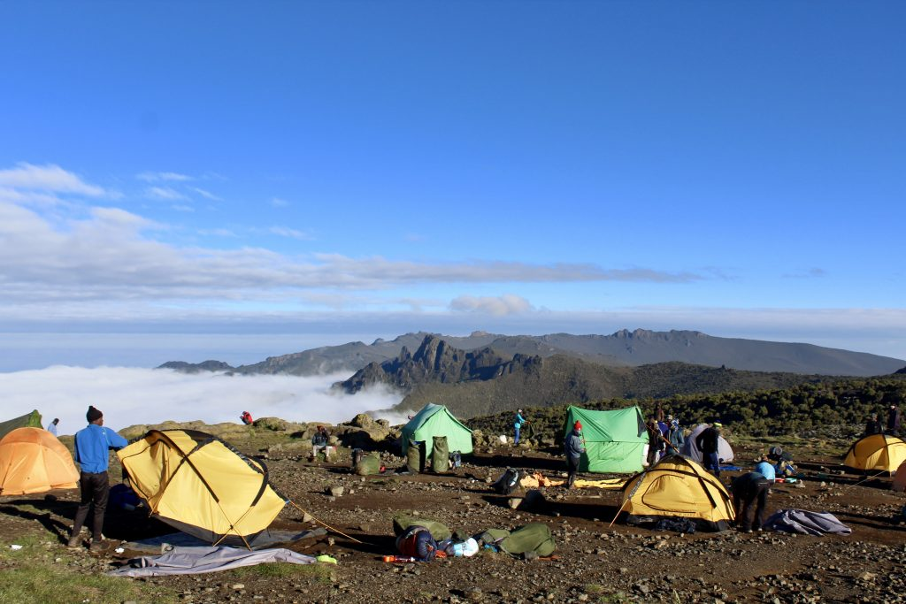 Tents scattered across Shira camp above the clouds on the Machame route to the summit of Kilimanjaro.