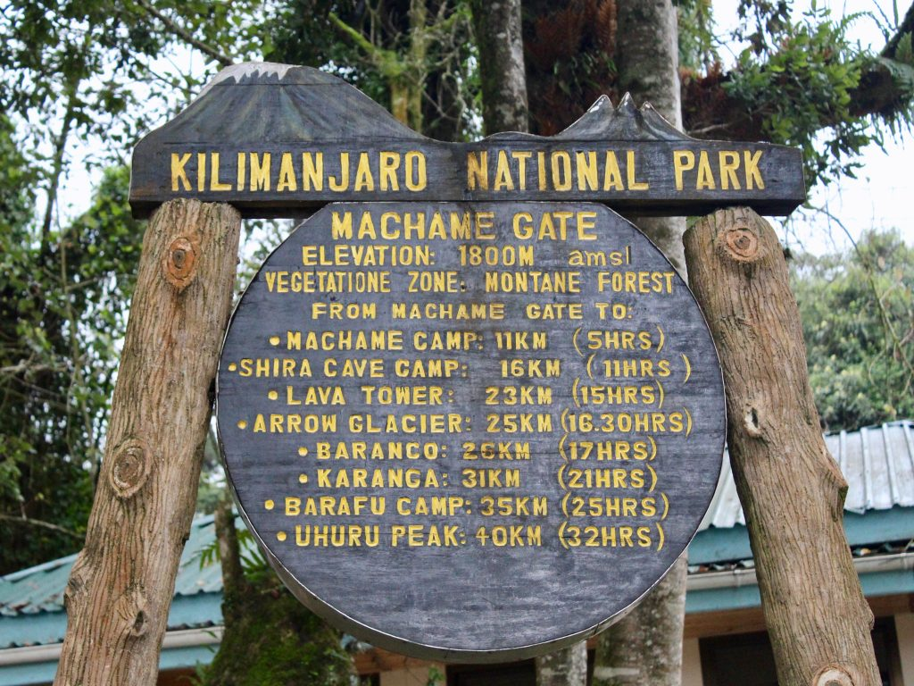 A sign detailing the milage and hours from the Machame gate to Uhuru peak for climbing Kilimanjaro